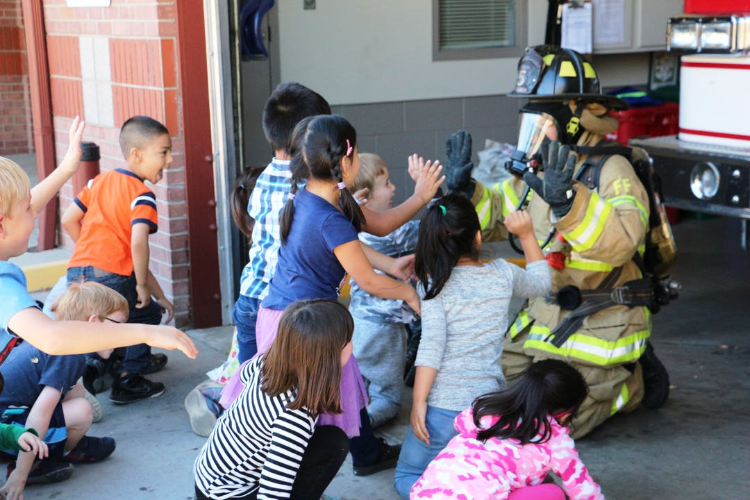 Children engage with a fire fighter.
