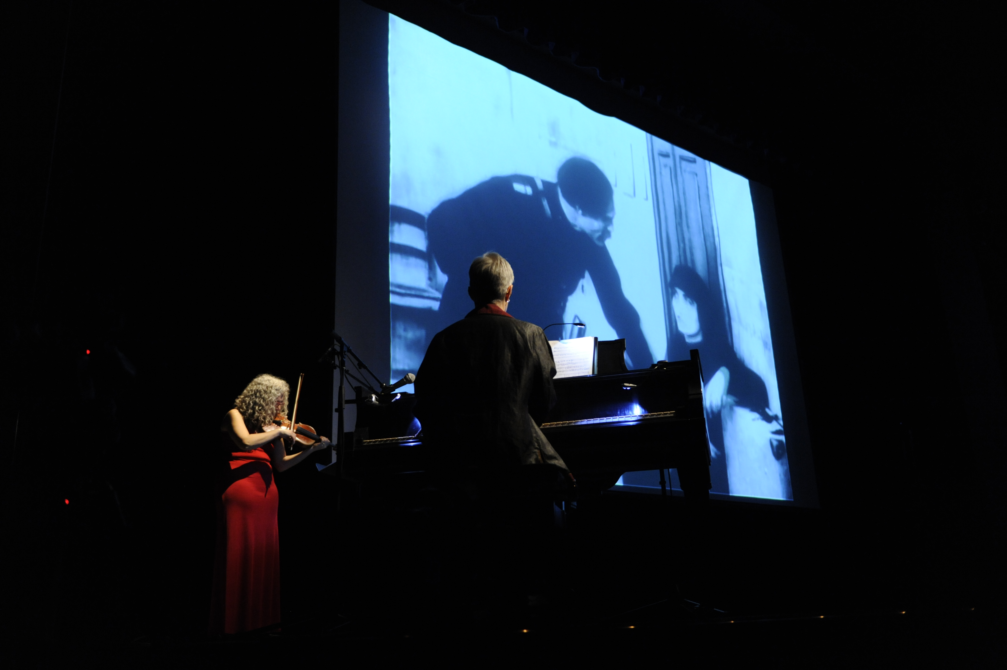 Picture of live score performance with black and white film screened behind